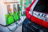 Selective Focus To The Car With Blurry Refilling The Car And Fuel At The Gas  Station Background poster