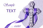 Easter background image of small ornate stone cross with purple satin ribbon and parchment paper on
