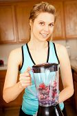 Young woman with a blender filled with berries