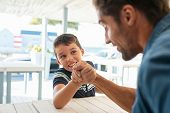 Happy father and smiling boy arm wrestling for fun. Man competing in arm wrestling with cheerful you poster