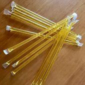 Yellow Bee Sticks Lie Beautifully On Wooden Kitchen Table, Tasty Organic Honey Dessert. The Photo Co poster