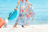 Travel Plan. Hand Women Traveler Holding Orange Luggage Walking On The Beach. Traveler And Tourism P poster