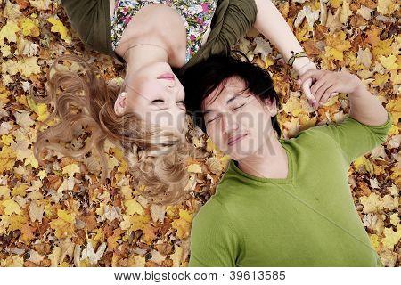 Beautiful Loving Couple Sleep On Autumn Leaves