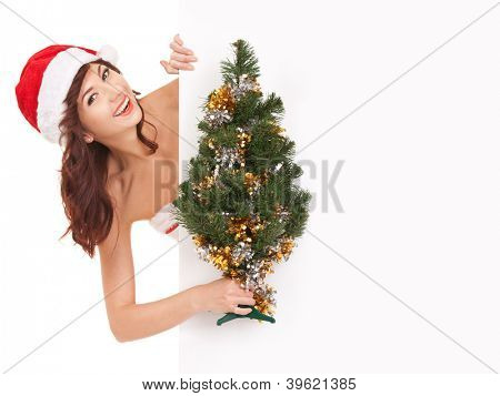 Santa woman with christmas tree peek behind the white blank board