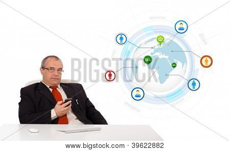 businessman sitting at desk and holding a mobilephone with globe and social icons, isolated on white