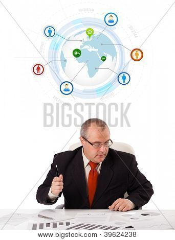 businessman sitting at desk with a globe and social icons, isolated on white