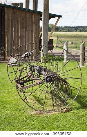 Old, rusty farm machinery hay rake near farm