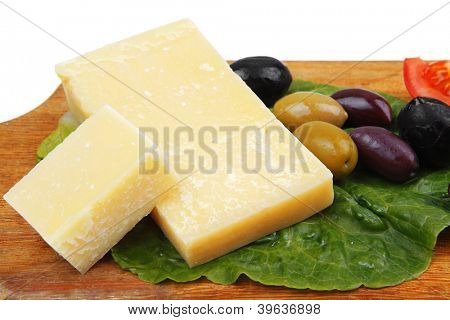 gold swiss cheese on wooden platter with olives and tomato isolated over white background