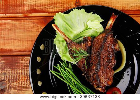 sawory on black: grilled ribs on plate over wooden table