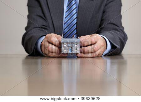 Real estate concept, businessman holding model house sitting at a desk