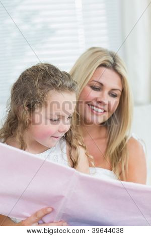 Smiling daughter and mother reading book together in living room