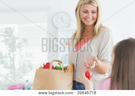 Madre pasando tomate a niño de bolsa de papel de la tienda de comestibles en la cocina