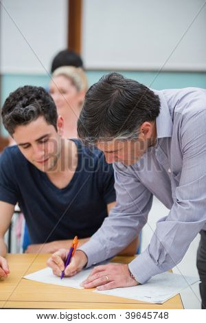Teacher making note on students work in classroom