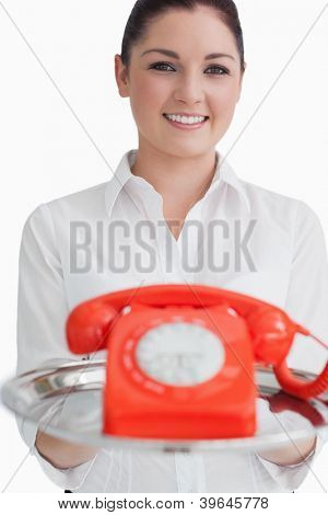 Smiling woman holding a silver tray with a red telephone