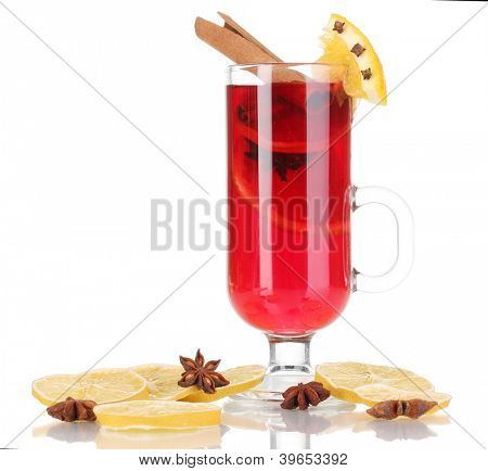 Fragrant mulled wine in glass with spices and oranges around isolated on white