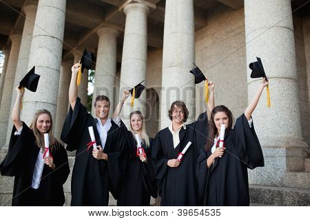 Graduates holding up their hats in front of the university