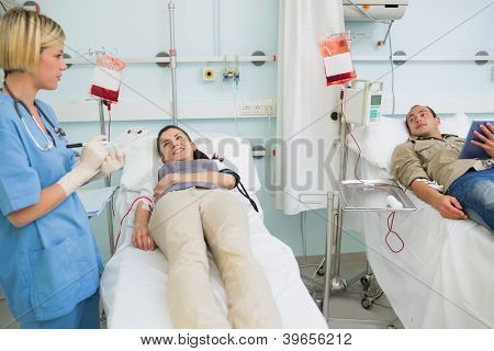 Two transfused patients looking at a nurse in hospital ward