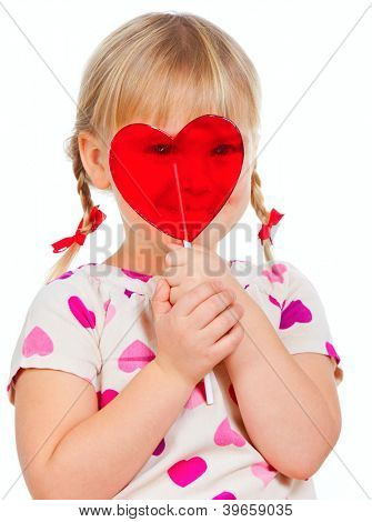 Cute little girl looking through big red heart shaped lolly pop candy