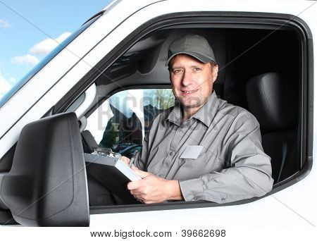 Smiling truck driver in the car. Delivery cargo service.