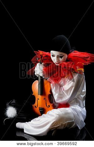 Sad Pierrot sitting on the floor with an old violin