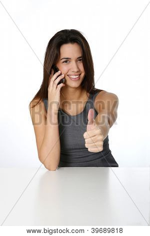 Young woman with smartphone showing thumb up