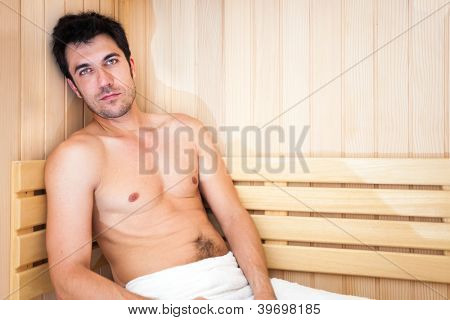 Handsome man having a steam bath in a sauna