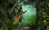 stock photo of archer  - a hunter in a hooded cape passes through the forest - JPG