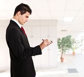 stock photo of mustering  - Businessman writing something on a clipboard - JPG