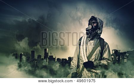 Man in gas mask against disaster background. Pollution concept