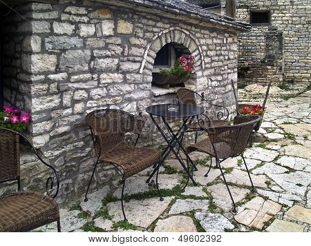 Chairs and table on stone patio in Greece