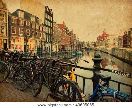 Amsterdam. The Singel is one of the numerous canals in Amsterdam, Netherlands.  Photo in retro style. Paper texture.