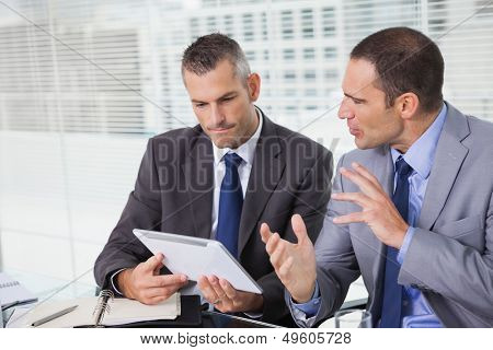 Serious businessmen analyzing documents on their tablet in bright office
