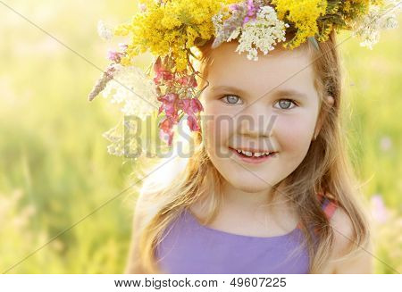Happy smiling 3 years old girl in colorful wild flowers wreath on a sunny summer meadow field