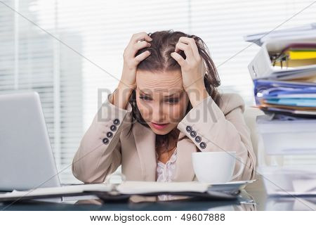 Nervous businesswoman pulling her hair out in her bright office