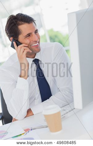 Smiling businessman on the phone looking at his computer in his office
