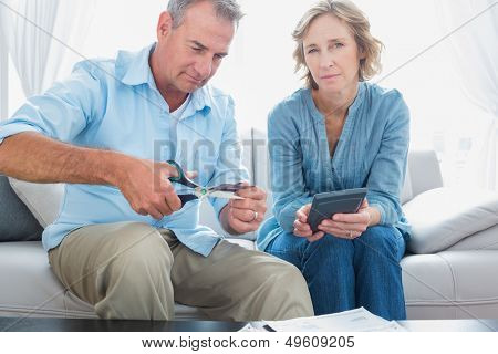 Husband cutting credit card in half with wife looking at camera at home in the living room