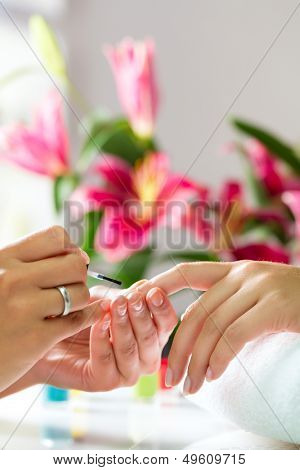 Woman in a nail salon receiving a manicure by a beautician