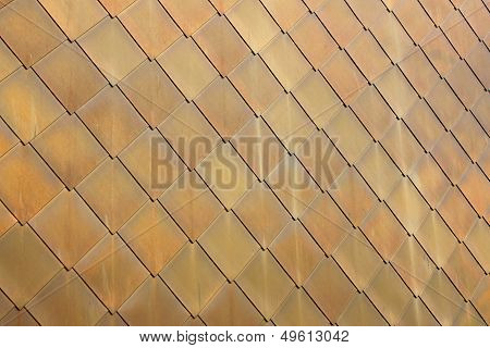 Gold-coloured metal scales on modern building #1