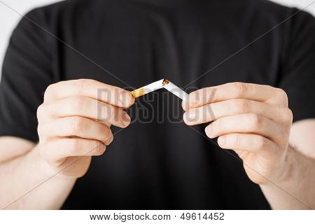 close up of man breaking the cigarette with hands