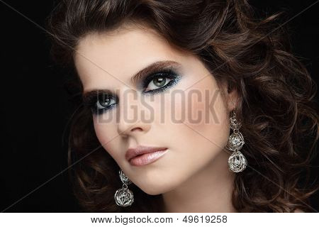 Portrait of young beautiful woman with stylish sparkly make-up and long curly hair