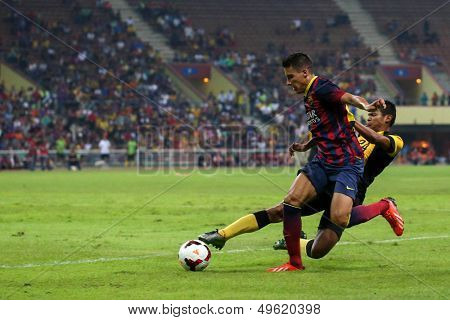 KUALA LUMPUR - AUGUST 10: Malaysia's N.M. Shahrul (24) tackles Barcelona's Cristian Tello (maroon/blue) in a friendly match at the Shah Alam Stadium on Aug 10, 2013 in Malaysia. Barcelona wins 3-1.