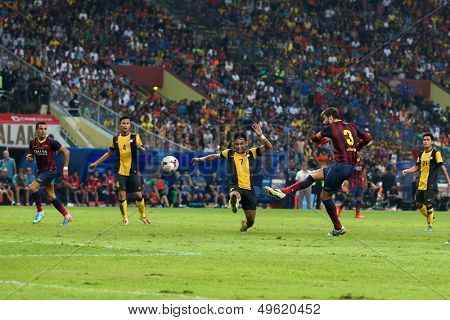 KUALA LUMPUR - AUGUST 10: FC Barcelona's Gerard Pique (3) scores in a friendly match against Malaysia at the Shah Alam Stadium on August 10, 2013 in Kuala Lumpur, Malaysia. Barcelona wins 3-1.