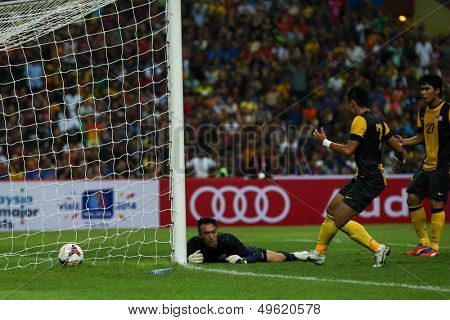 KUALA LUMPUR - AUGUST 10: Malaysia's goalkeeper Khairul Fahmi and defender M. A Zafuan (7) fail to stop Barcelona's goal at the Shah Alam Stadium on Aug 10, 2013 in Malaysia. FC Barcelona wins 3-1.