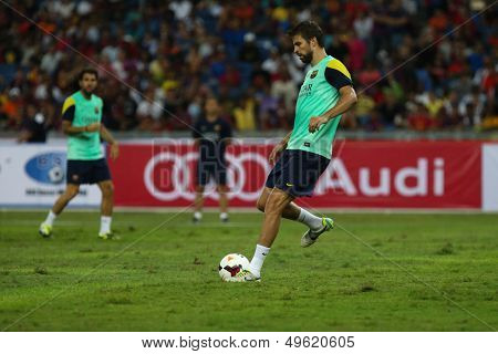 KUALA LUMPUR - AUGUST 9: FC Barcelona 's Gerard Pique practices during training at the Bukit Jalil Stadium on August 09, 2013 in Malaysia. FC Barcelona is on an Asia Tour to Malaysia and Thailand.