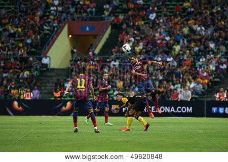 KUALA LUMPUR - AUGUST 10: FC Barcelona 's Jordi Alba (maroon/blue) heads the ball in a game against Malaysia at the Shah Alam Stadium on August 10, 2013 in Malaysia. FC Barcelona wins 3-1.