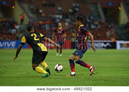 KUALA LUMPUR - AUGUST 10: FC Barcelona 's Neymar (maroon/blue) dribbles past Malaysia's Mahalli (2) in game played at the Shah Alam Stadium on August 10, 2013 in Malaysia. FC Barcelona wins 3-1.