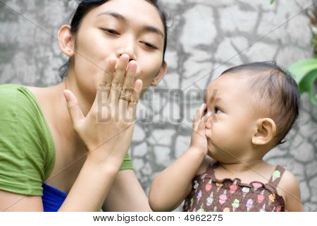 Mother Teaching Baby Girl A Goodbye Kiss