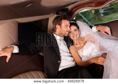 Happy couple sitting in limousine on wedding-day.