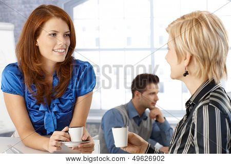 Businesswoman on coffee break, talking to colleague, smiling.
