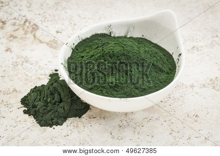 small bowl of Hawaiian spirulina powder against a ceramic tile  background